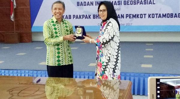 Walikota Kotamobagu Ir Hj Tatong Bara saat menerima penghargaan dari Badan Informasi Geopasial
