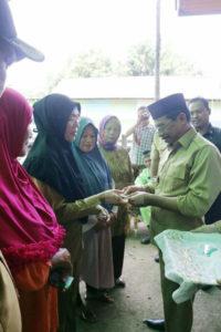 Bupati Boltim saat menyerahkan secara simbolis Kartu Indonesia Sehat (KIS) kepada sejumlah Warga yang berhak menerimah yang berada di dua kecamatan Motongkad dan Nuangan