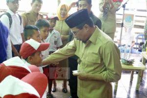 Bupati Boltim saat menyerahkan secara simbolis Kartu Indonesia Pintar (KIP) kepada sejumlah Siswa SD, SMP dan SMA sederajat yang ada di dua kecamatan Motongkad dan Nuangan
