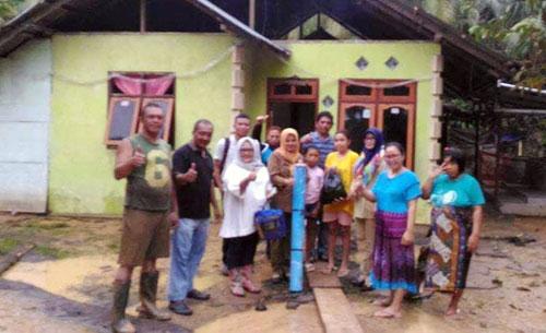 Ketua Tim Penggerak PKK Boltim saat menyerahkan bantuan kepada korban banjir di Desa Molobog