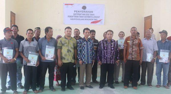 Asisten Bidang Pemerintah dan Kesos Pemkab Boltim, Amin Musa SH MH saat mewakili Bupati Boltim untuk menyerahkan sertificate kepada warga Desa Togid