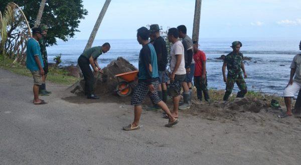 Tampak DANDIM 1303-BM Letkol INF Sigit Dwi Cahyono, SE masih menggunakan seragam lengkap turun langsung mengangkut pasir untuk pembangunan kantor tiga pilar TMMD ke- 101 di Desa Pakuku Jaya